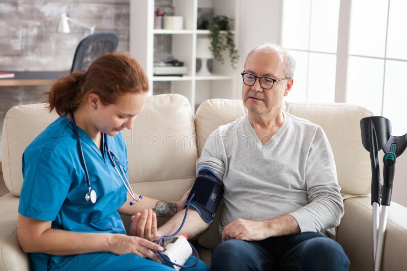 Female doctor reading blood pressure of old man. Female doctor reading blood pressure of old men in nursing home using digital device. Nurse and patient sitting stock photos