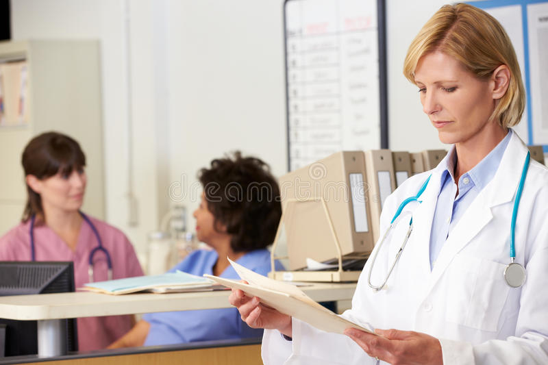 Female Doctor Reading Patient Notes At Nurses Station stock images