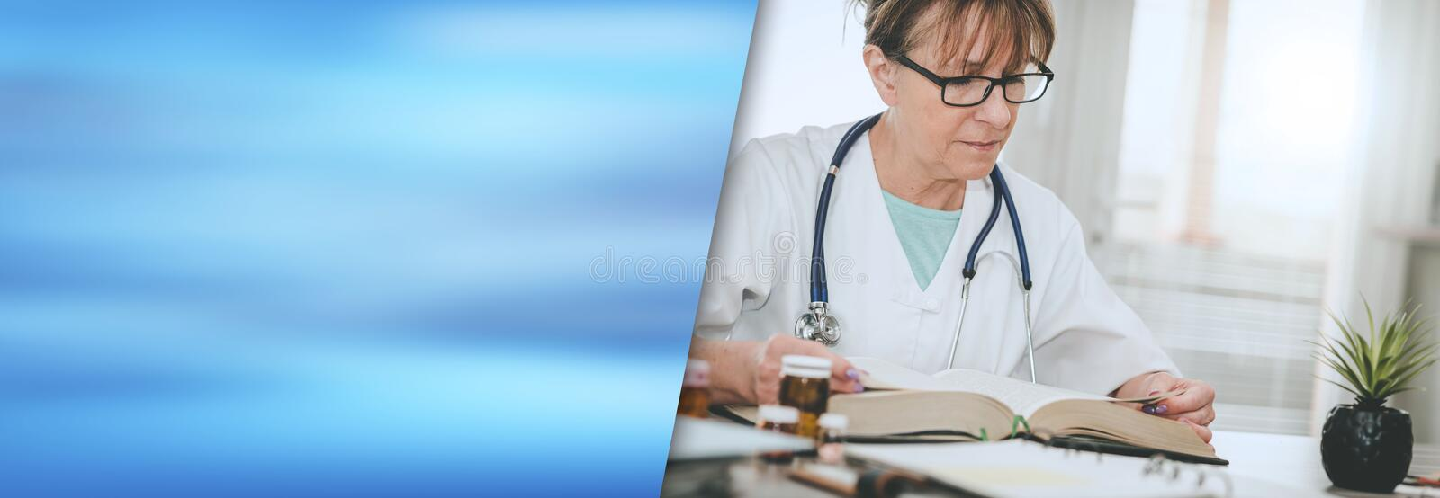 Female doctor reading a textbook; panoramic banner stock photo