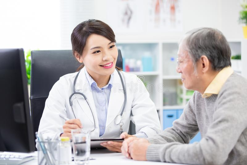 Female doctor see elder patient. And discuss with him patiently royalty free stock photography