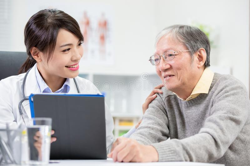 Female doctor see elder patient. And console him not worry royalty free stock photo