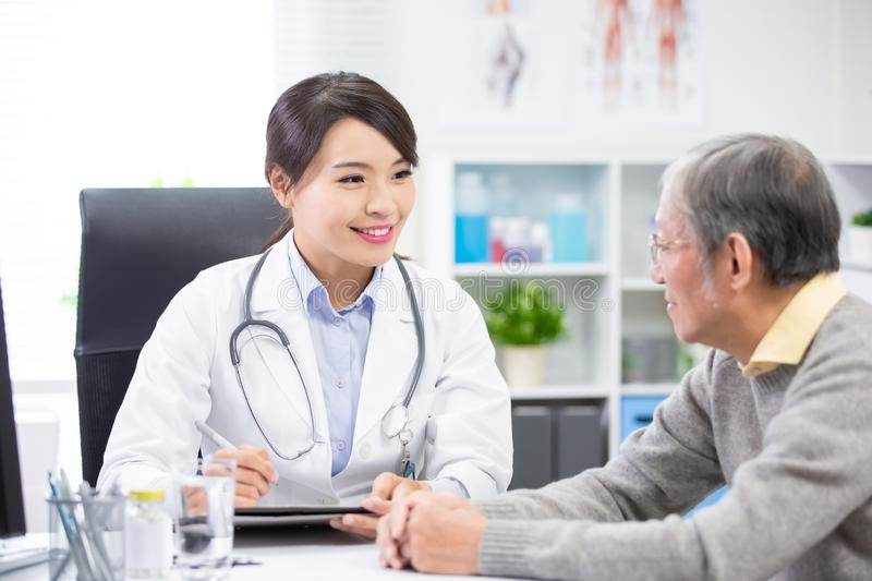 Female doctor see elder patient. And discuss with him patiently stock photography