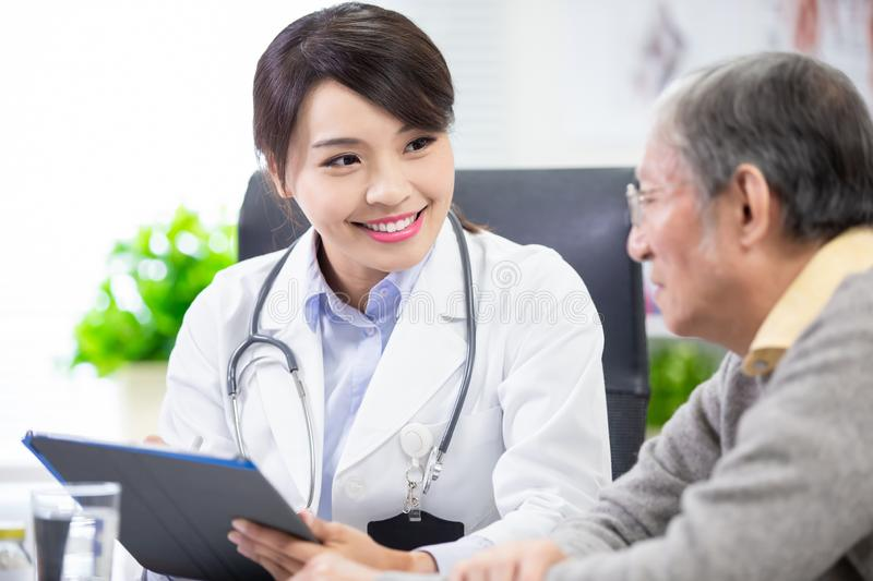 Female doctor see elder patient. And write down something on digital tablet royalty free stock photography