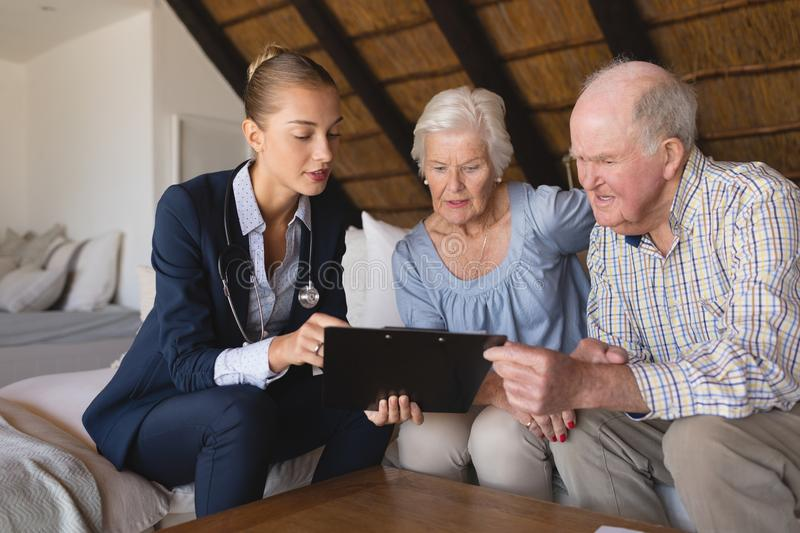 Female doctor and senior couple discussing over clipboard. Front view of a female doctor and senior couple looking and discussing over clipboard they hold in royalty free stock photos