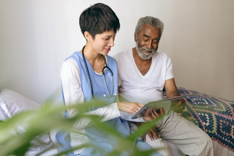 Female doctor and senior male patient using digital tablet at retirement home. Front view of Asian female doctor and senior African-american  male patient using royalty free stock photos