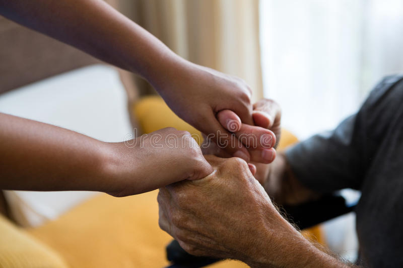 Female doctor and senior man holding hands in nursing home royalty free stock photos