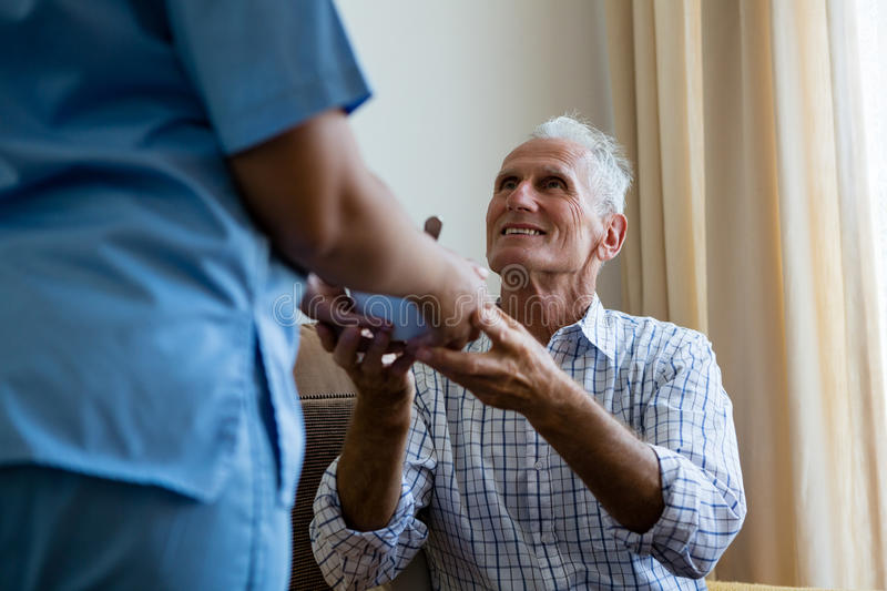Female doctor serving food to senior man at retirement home. Midsection of female doctor serving food to senior men at retirement home royalty free stock photography