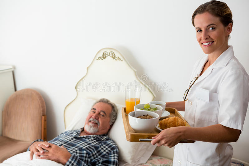 Female doctor serving food to senior patient relaxing on bed in retirement home royalty free stock photography