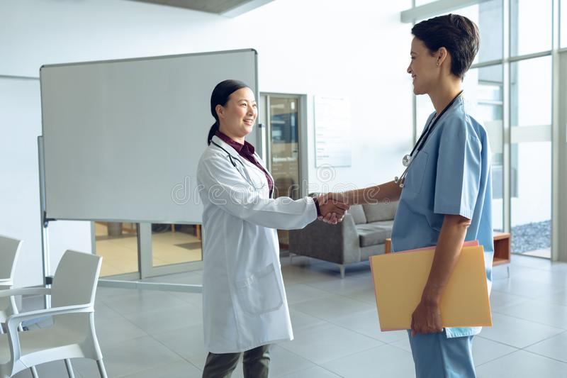 Female doctor shaking hands with nurse in the hospital stock image