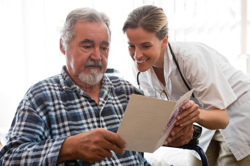 Female doctor showing greeting card to patient sitting on wheelchair royalty free stock photography