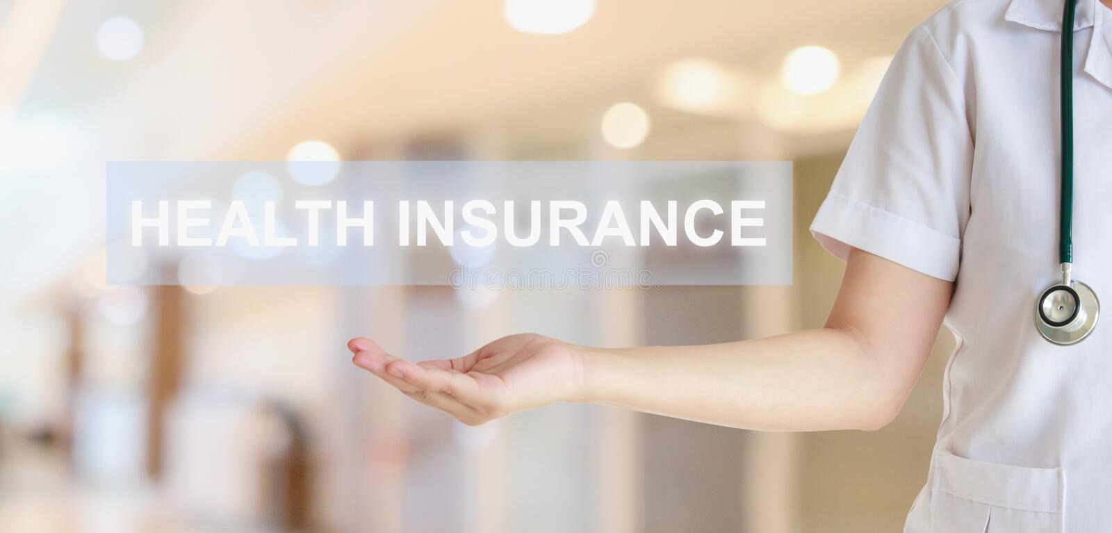 Female doctor showing Health Insurance text with blur hospital. Room background healthcare concept stock image