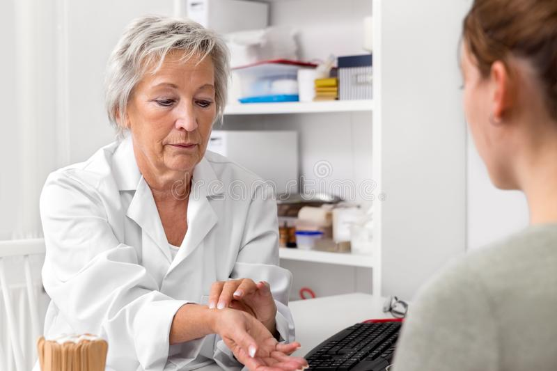 Female doctor showing the heart rate or pulse check up to a patient royalty free stock images