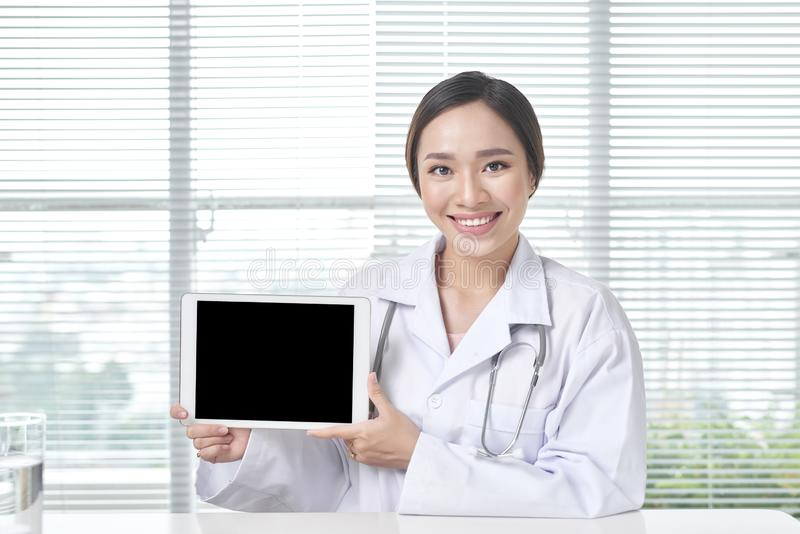 Female doctor showing tablet with blank screen to patient at office stock photos