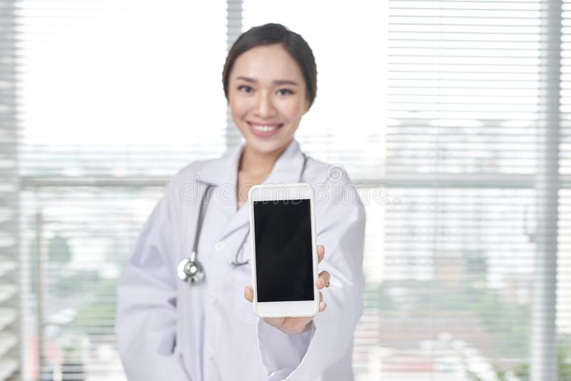Female doctor shows blank screen of smartphone royalty free stock images