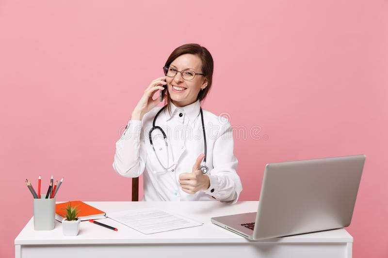 Female doctor sit at desk work on computer with medical document hold cellphone in hospital isolated on pastel pink. Background. Woman in medical gown glasses stock photography
