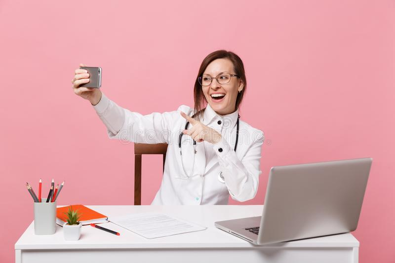 Female doctor sit at desk work on computer with medical document hold cellphone in hospital isolated on pastel pink. Background. Woman in medical gown glasses royalty free stock image