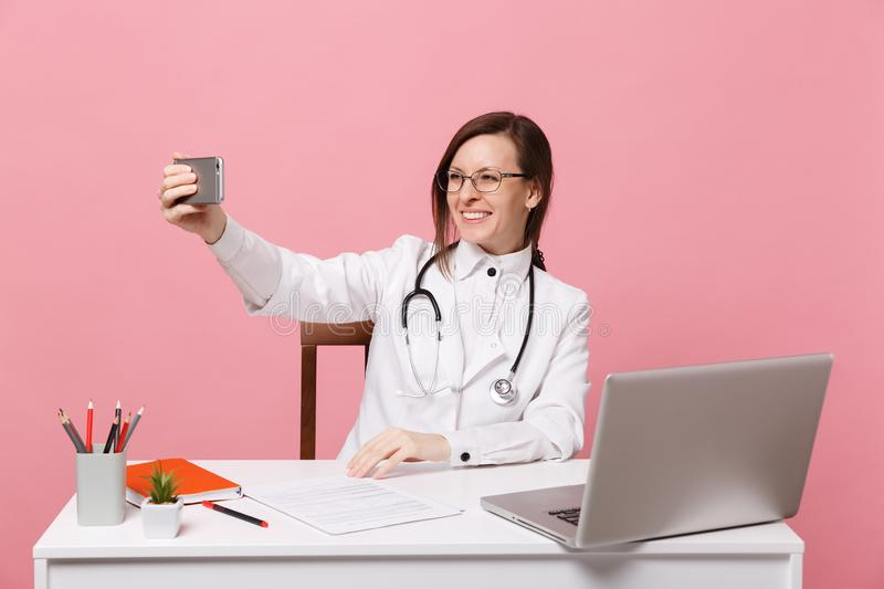 Female doctor sit at desk work on computer with medical document hold cellphone in hospital isolated on pastel pink. Background. Woman in medical gown glasses stock image