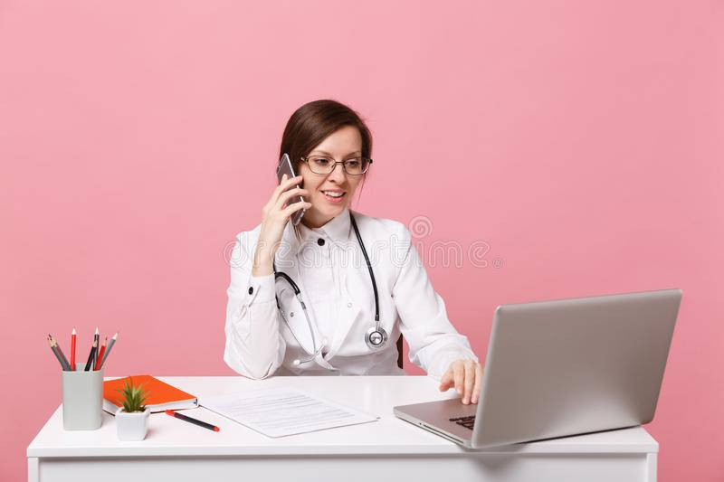 Female doctor sit at desk work on computer with medical document hold cellphone in hospital isolated on pastel pink. Background. Woman in medical gown glasses royalty free stock images