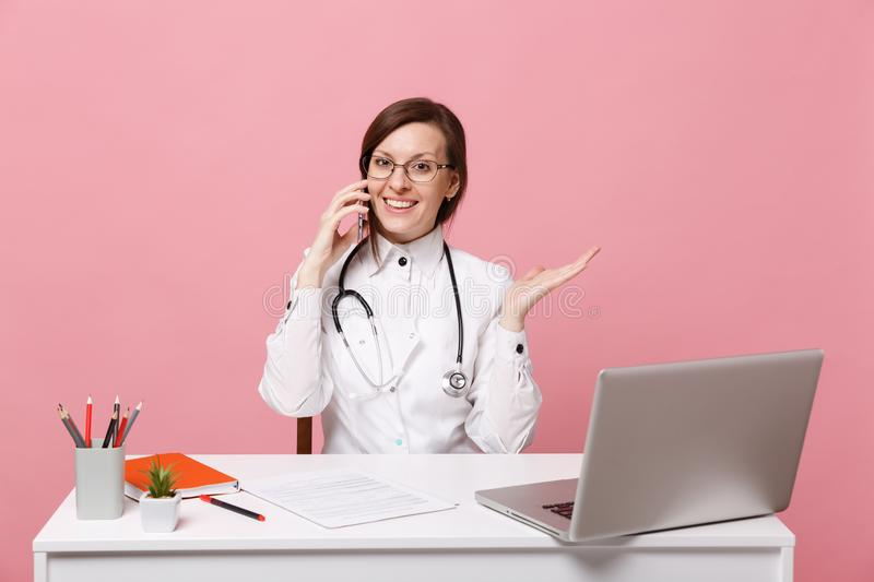 Female doctor sit at desk work on computer with medical document hold cellphone in hospital isolated on pastel pink. Background. Woman in medical gown glasses royalty free stock photos