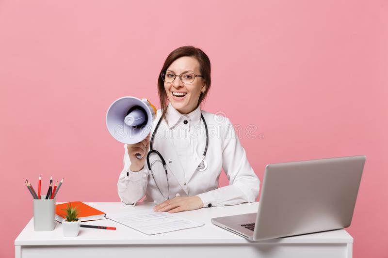 Female doctor sit at desk work on computer with medical document hold megaphone in hospital isolated on pastel pink royalty free stock photos