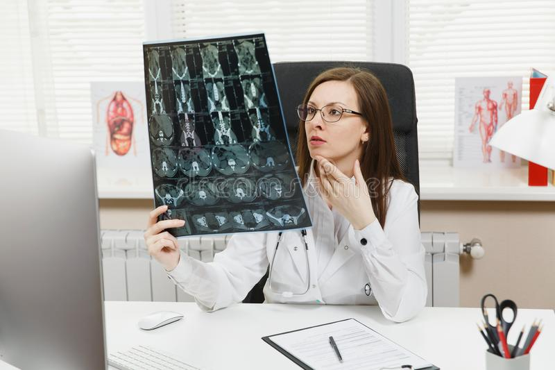 Female doctor sitting at desk with computer, film x-ray the brain by radiographic image ct scan mri in light office in. Hospital. Woman in medical gown in stock image