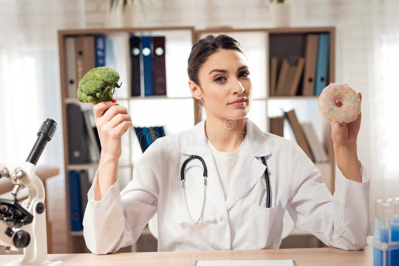 Female doctor sitting at desk in office with microscope and stethoscope. Woman is holding broccoli and donut. Female doctor in white gown sitting at desk in royalty free stock images
