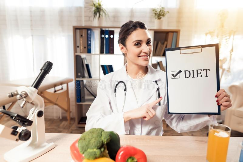 Female doctor sitting at desk in office with microscope and stethoscope. Woman is holding diet sign. Female doctor in white gown sitting at desk in office with stock image