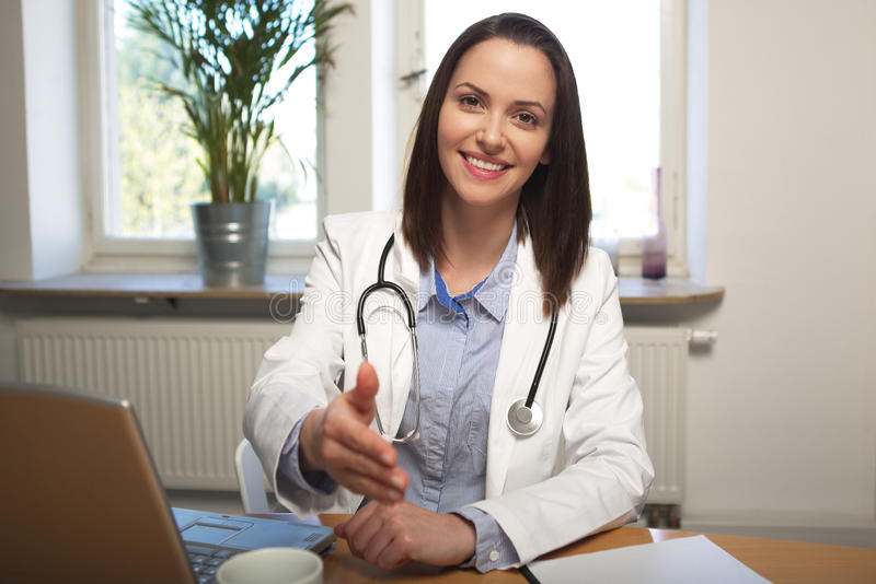 Female doctor is sitting at her desk and greets a patient royalty free stock photos
