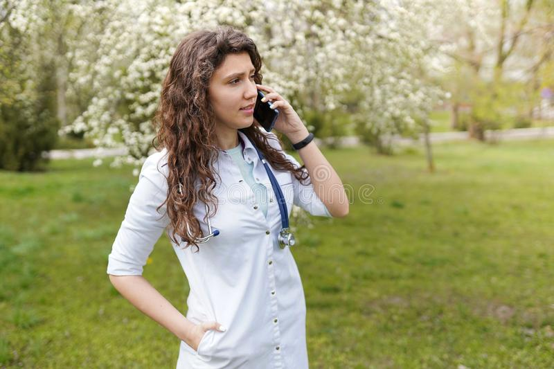 Female doctor speaking on mobile phone . medical background copy space . outdoors of a hospital in flower garden . Cheerful young stock photography