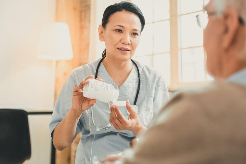 Female doctor with special equipment on her neck. Bottle of pills. Female doctor with special equipment on her neck talking to her old patient during appointment stock photos
