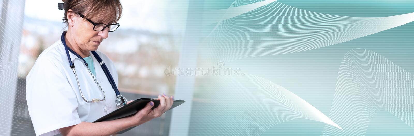Female doctor taking notes on clipboard; panoramic banner royalty free stock photo