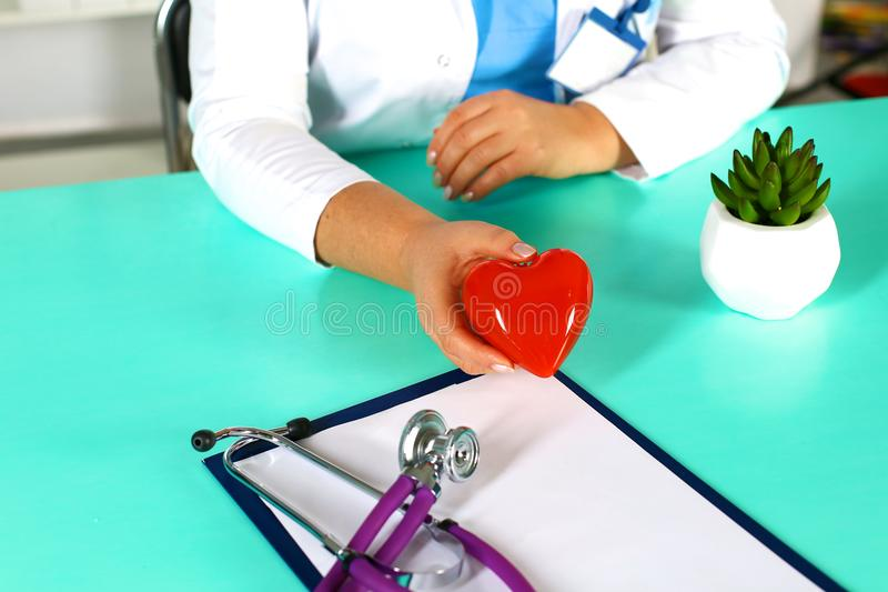Female doctor with stethoscope holding heart. Doctor and patient sitting in the background.  stock images