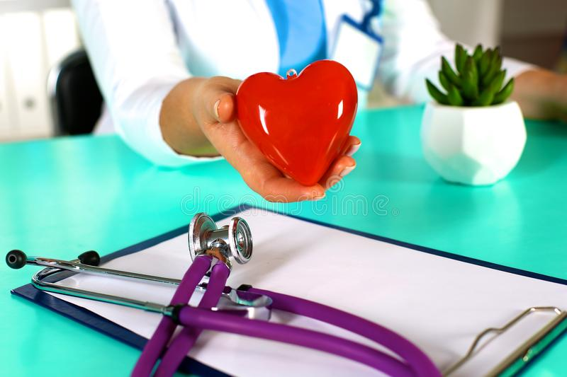 Female doctor with stethoscope holding heart. Doctor and patient sitting in the background.  royalty free stock images