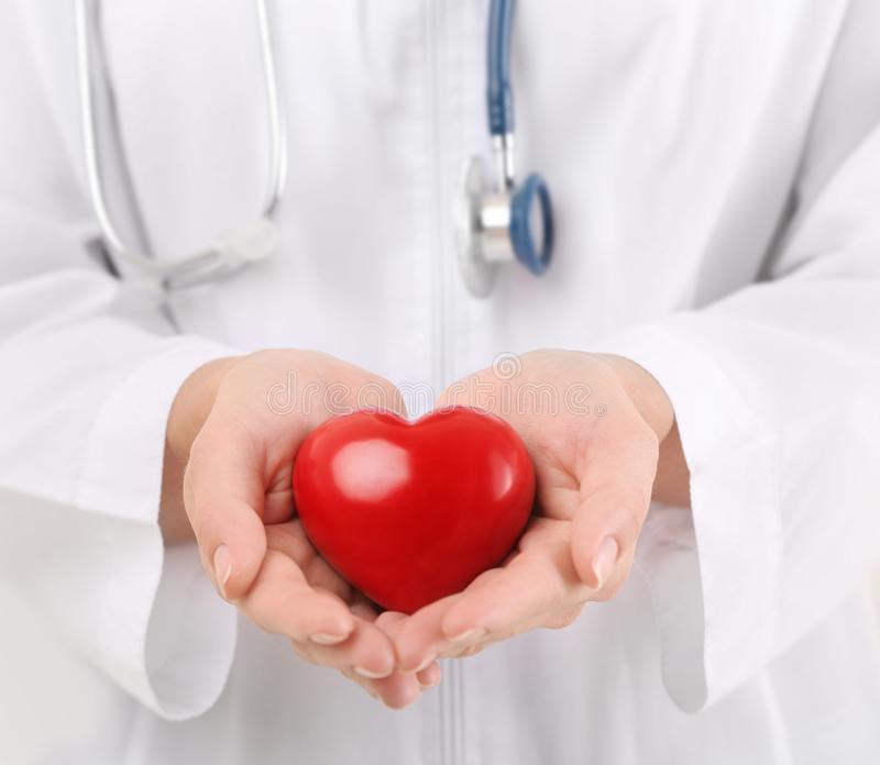 Female doctor with stethoscope holding heart,. Closeup stock photography