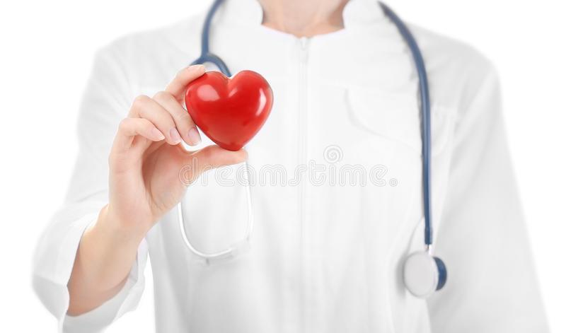 Female doctor with stethoscope holding heart. On white background stock photo