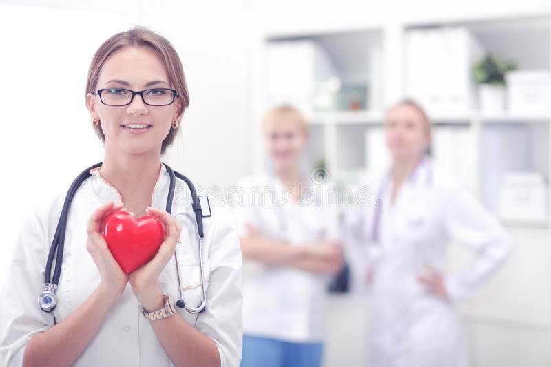 Female doctor with stethoscope holding heart in her arms. Healthcare and cardiology concept in medicine stock images