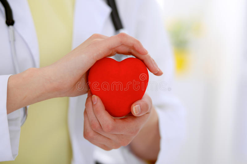 Female doctor with stethoscope holding heart. Patients couple sitting in the background royalty free stock images
