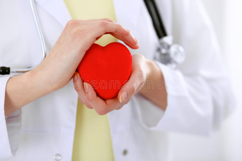Female doctor with stethoscope holding heart. Patients couple sitting in the background stock images