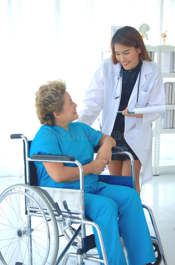Female doctor take care a senior patient on a wheelchair royalty free stock photo
