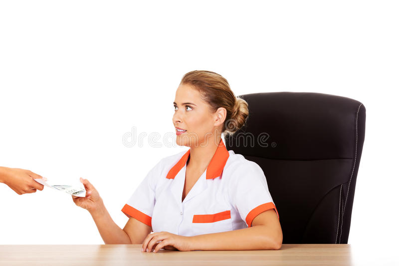 Female doctor take money from patient.  royalty free stock images