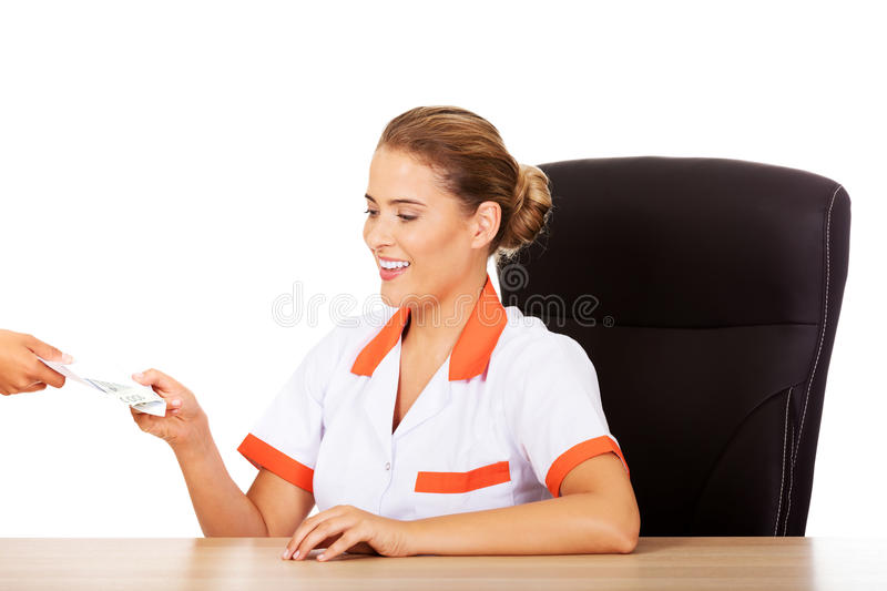 Female doctor take money from patient.  royalty free stock photos