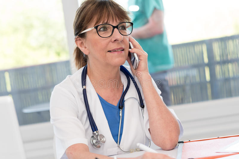 Female doctor talking on mobile phone. In clinical office royalty free stock images