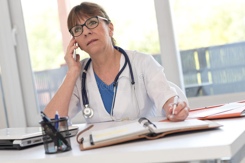 Female doctor talking on mobile phone. In medical office royalty free stock photography