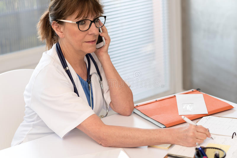 Female doctor talking on mobile phone. In medical office stock photos