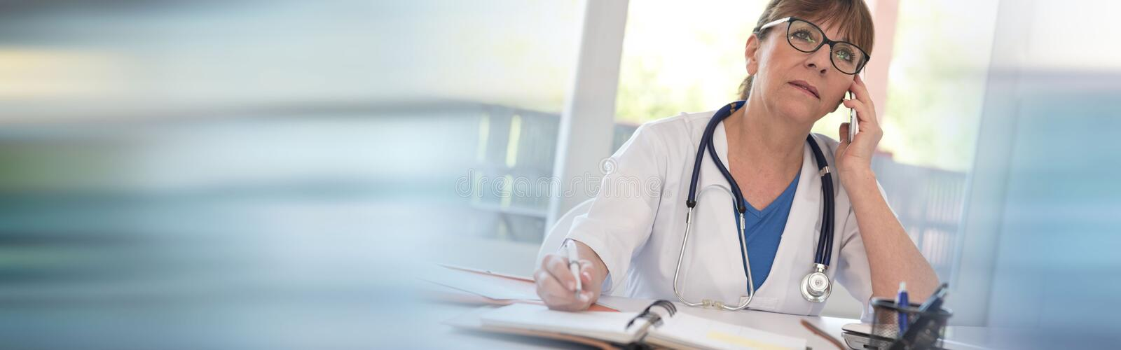 Female doctor talking on mobile phone. In medical office stock photo