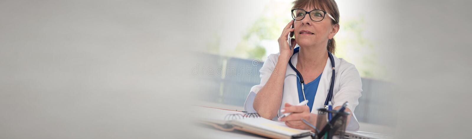 Female doctor talking on mobile phone stock images