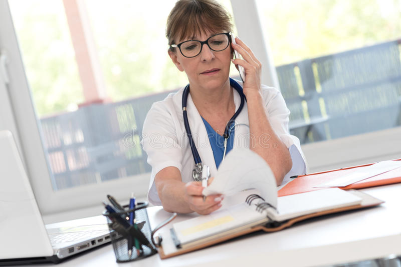 Female doctor talking on mobile phone. In medical office stock images