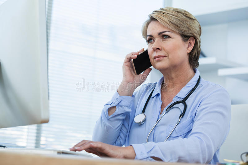 Female doctor talking on mobile phone while working over computer stock photography