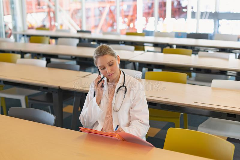 Female doctor talking on mobile phone while writing on a file in the medical seminar. High angle view of beautiful mature Caucasian female doctor talking on royalty free stock photos