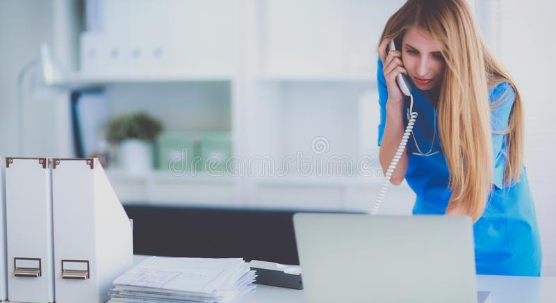 Female doctor talking on phone in diagnostic center.  royalty free stock image
